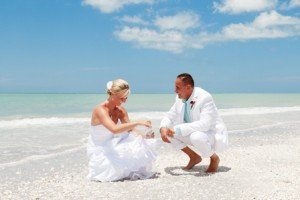 bride and groom pick up sea shells on sanibel island