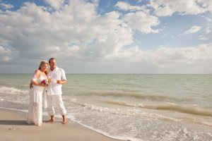 couple with champagne at their vow renewal on sanibel beach