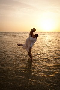 groom lifts his new bride at sunset on Captiva Island beach